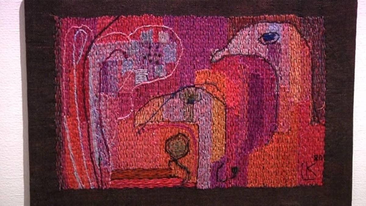 Tekstiilitaideteos seinällä.
