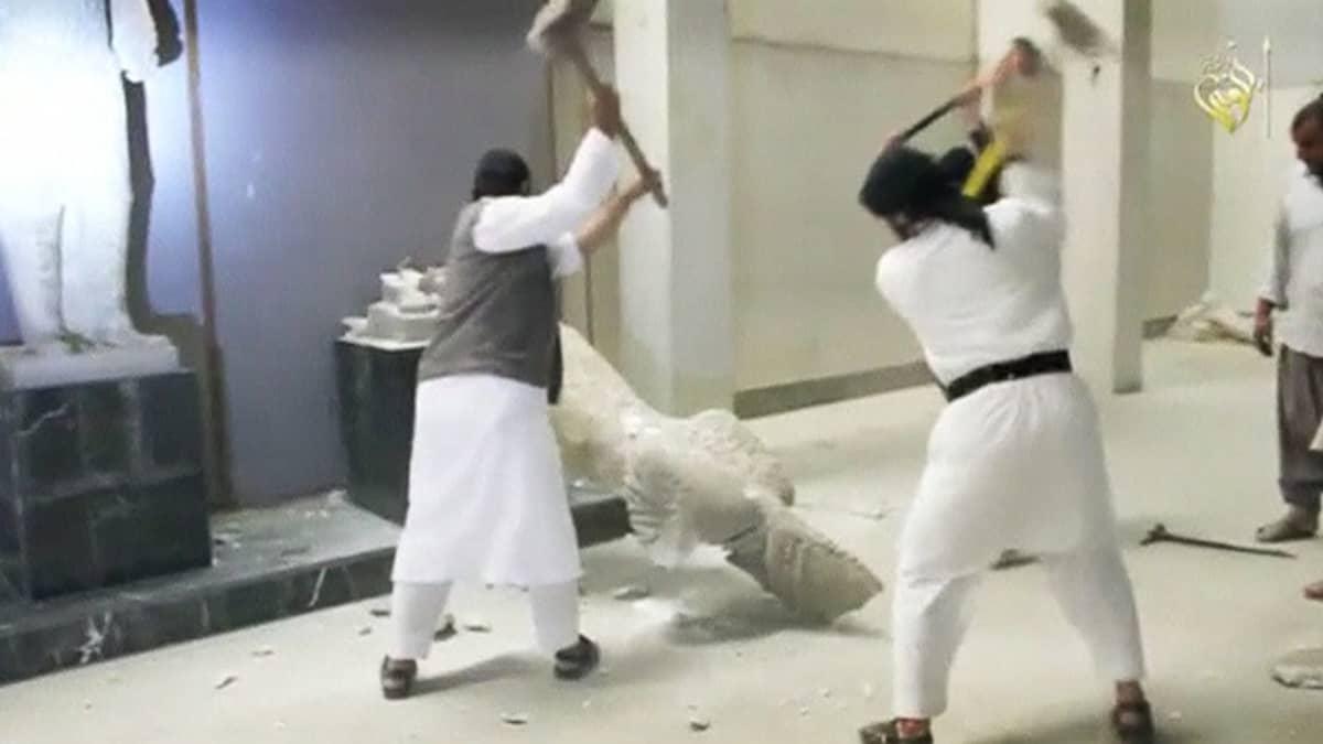 Miehiä tuhoamassa patsaita lekojen kanssa.
