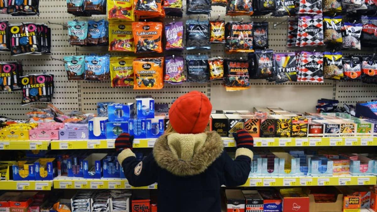 Lapsi ihailee herkkuja karkkihyllyllä kaupassa.