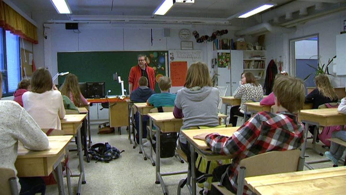 Oppilaita ja opettaja Viljakkalan koulun luokkahuoneessa