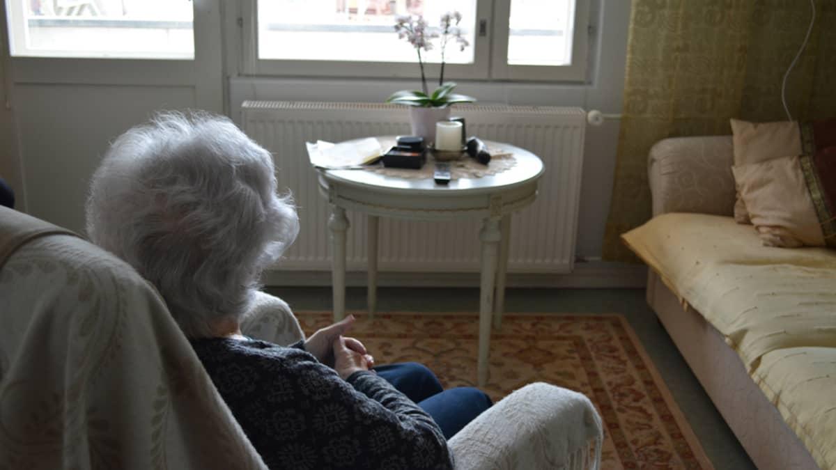 Vanha nainen istuu nojatuolissa ja katsoo ikkunasta ulos olohuoneessa.