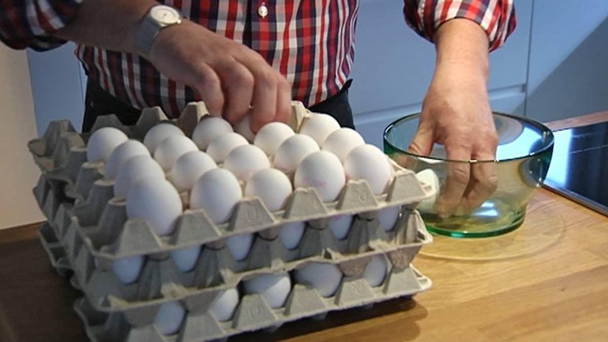 Mies laittaa kananmunia lasiseen kulhoon keittiössä.