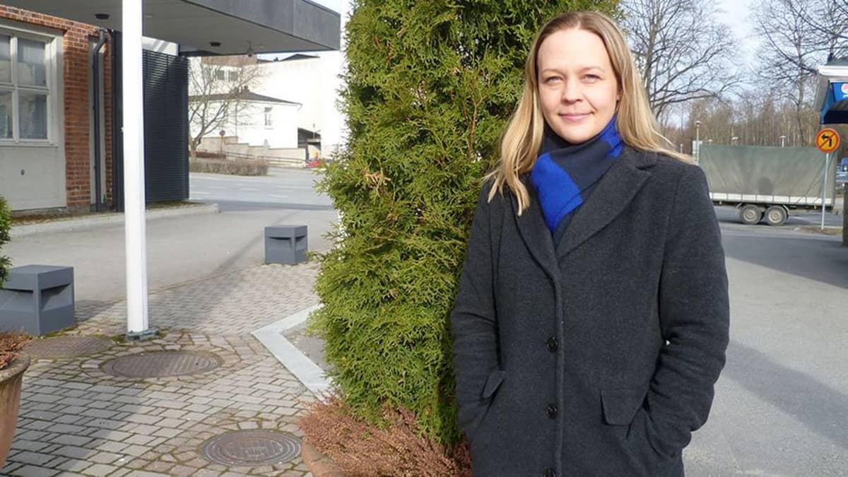 Nainen seisoo ulkona havupuun edessä.