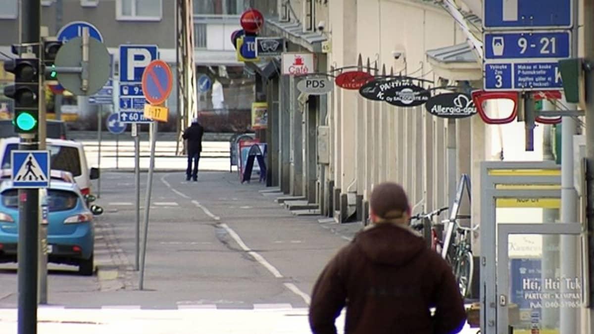 Liikehuoneistoja, jalkakäytävä ja autoja katukuvassa.