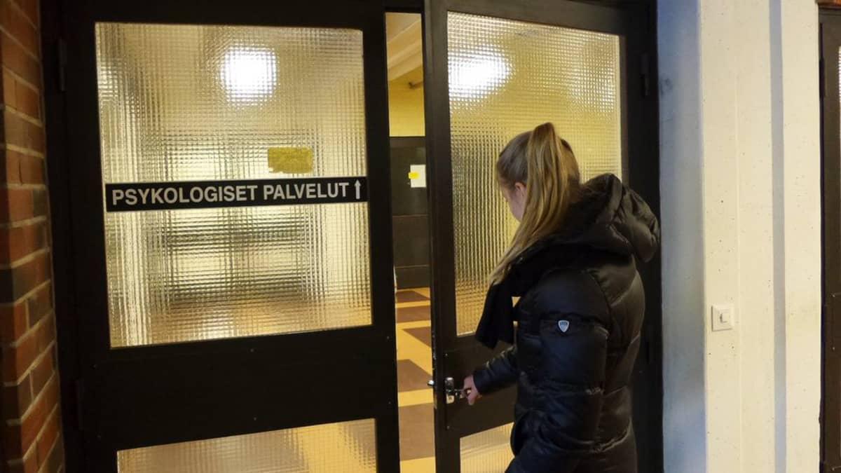 Nuori nainen avaamassa terveyskeskuksen ovea.