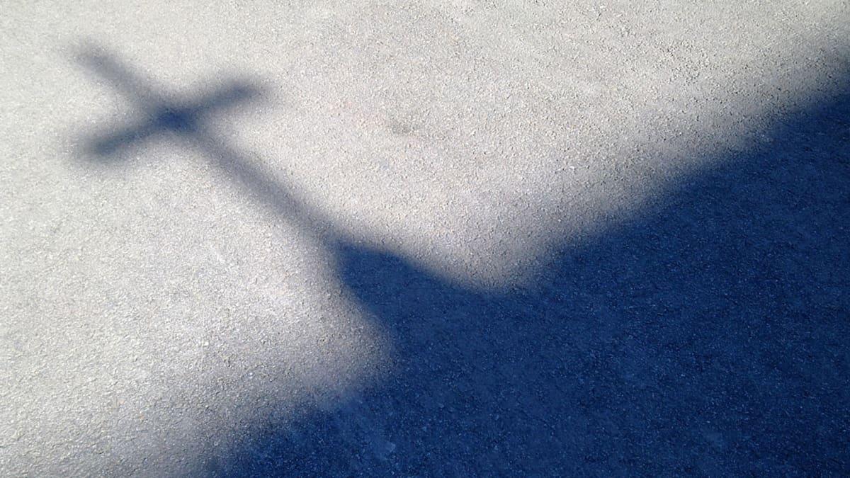 Asfaltista heijastuva ristin varjo.