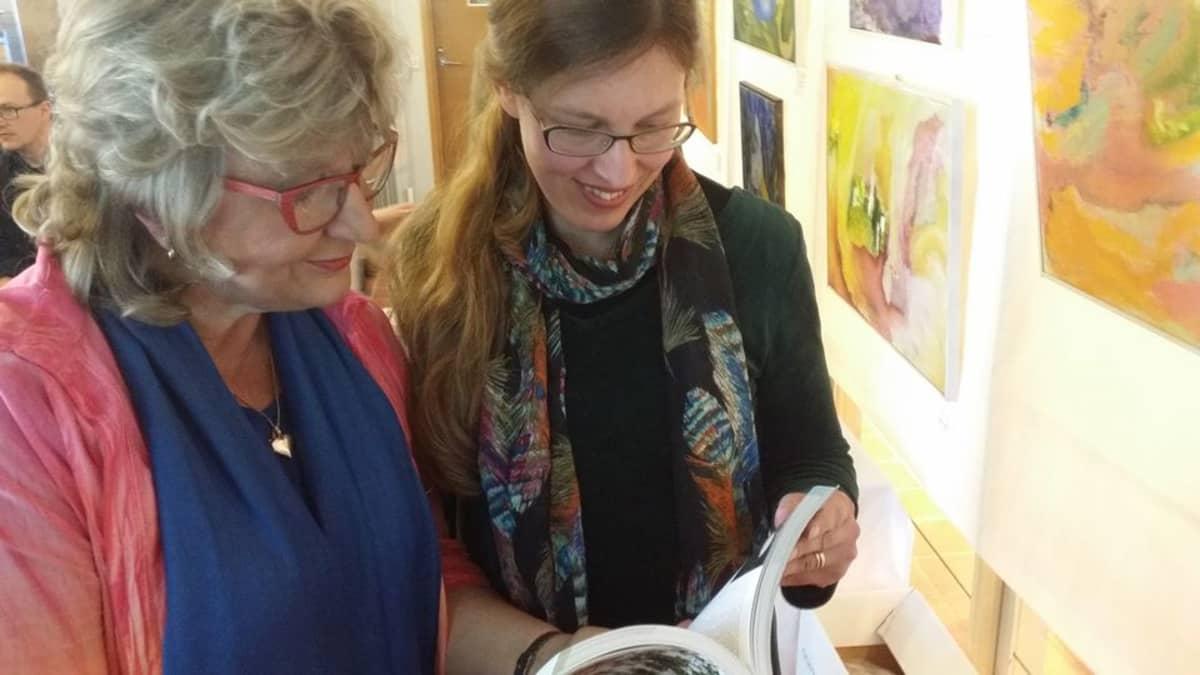 Ann-Mari Rannikko ja Mia Rönkä lehteilevät tuoretta opasta.