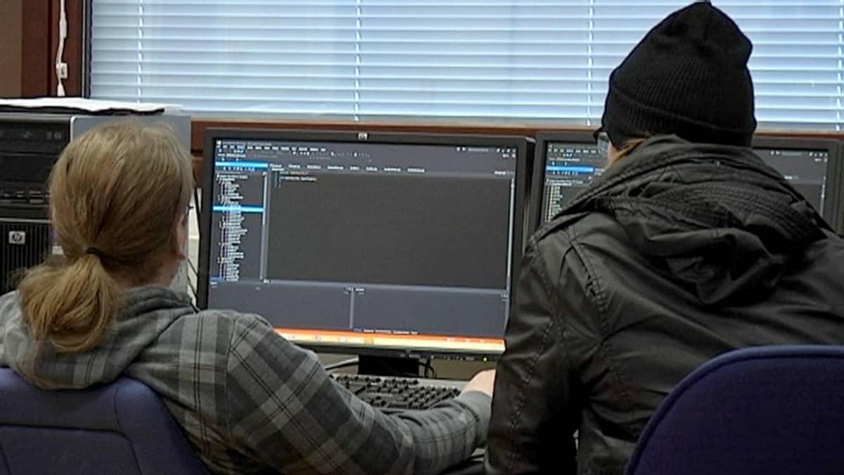 Kaksi ihmistä työskentelee tietokoneella.