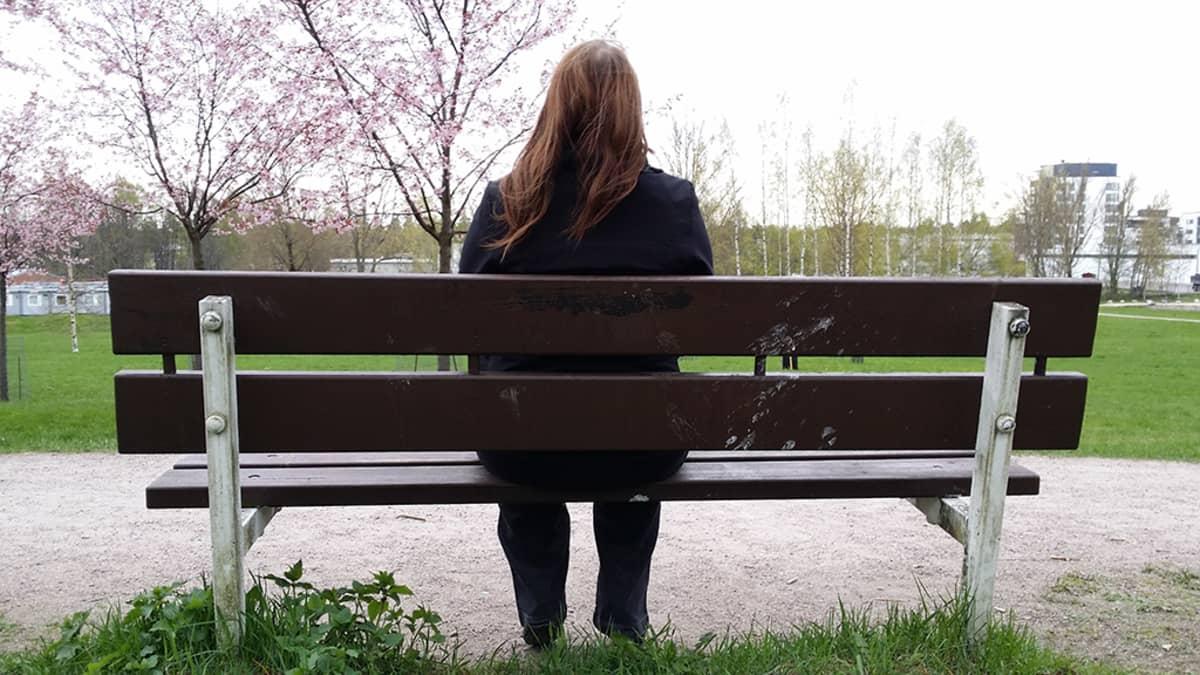 Nuori nainen puistonpenkillä.