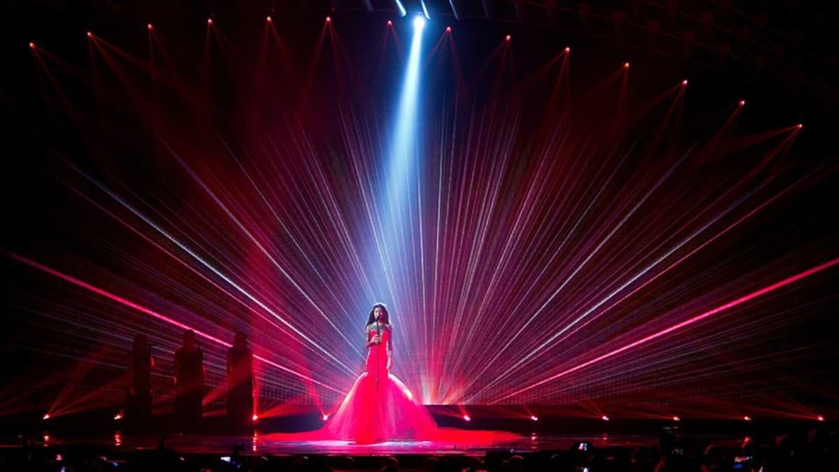 Punamekkoinen nainen lavalla.