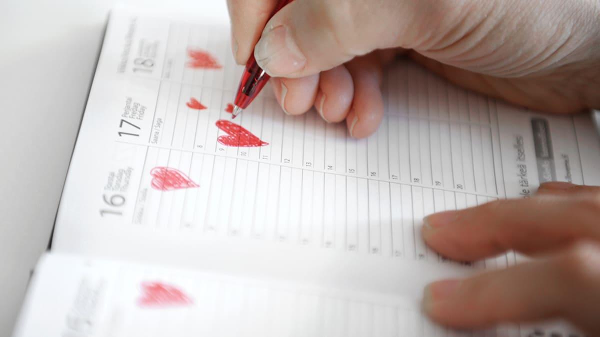 Nuori nainen piirtää sydämiä kalenteriinsa.