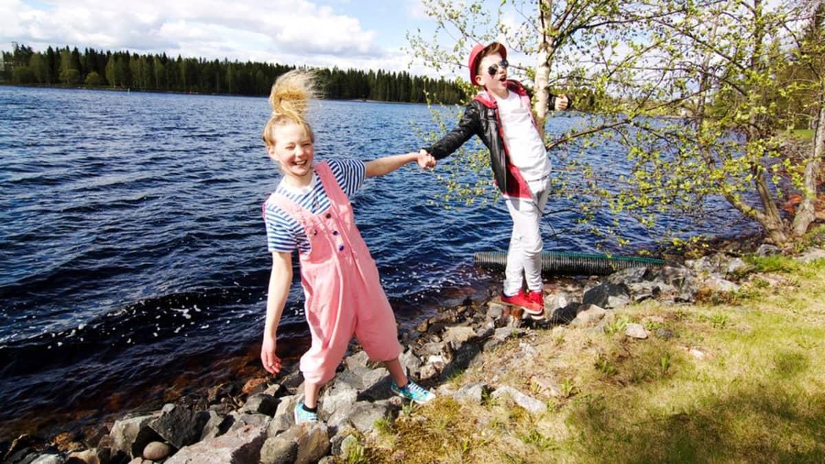 Kaksi nuorta näyttelijää joen rannassa.