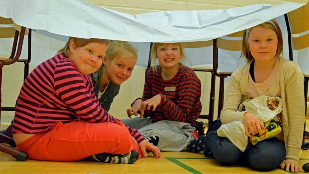 Neljä lasta tuoleista ja lakanasta tehdyssä majassa.