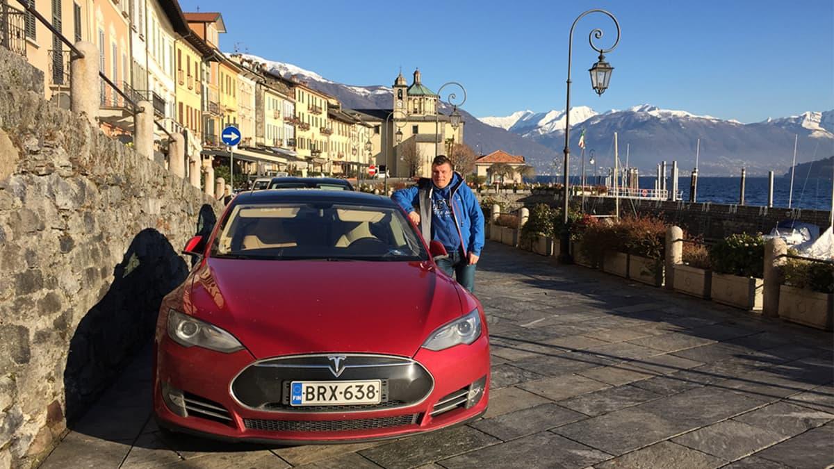 Mies ja punainen Tesla-sähköauto.