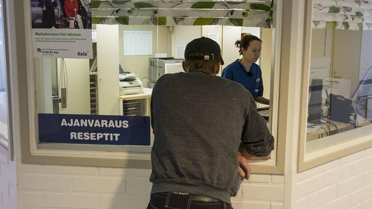 Mies varaamassa aikaa terveyskeskuksessa.