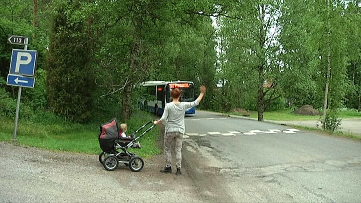 Nainen lastenrattaiden kanssa viittelöi bussille Teiskon kirkolla.