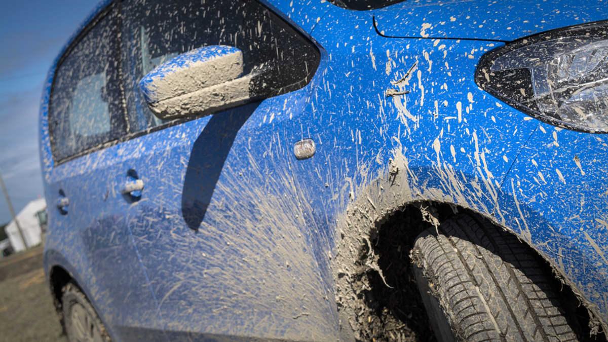 Suviseurojen sininen huoltoauto kuivuneen ravan ja mudan peitossa.