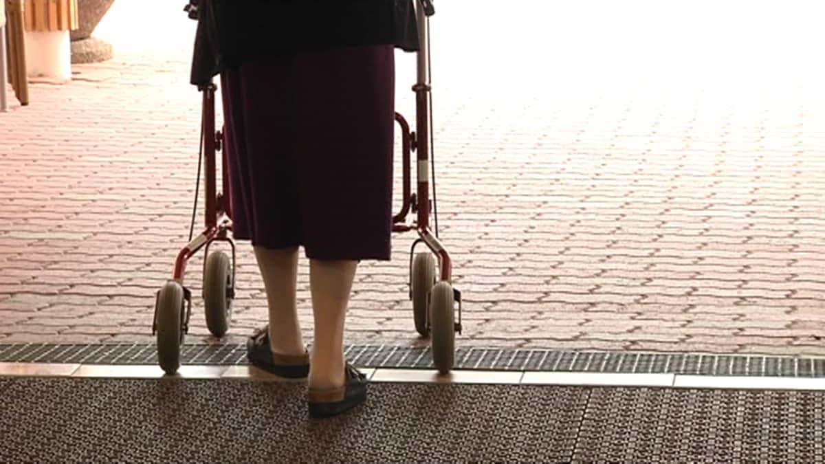 Iäkäs nainen kulkee rollaattorin kanssa.