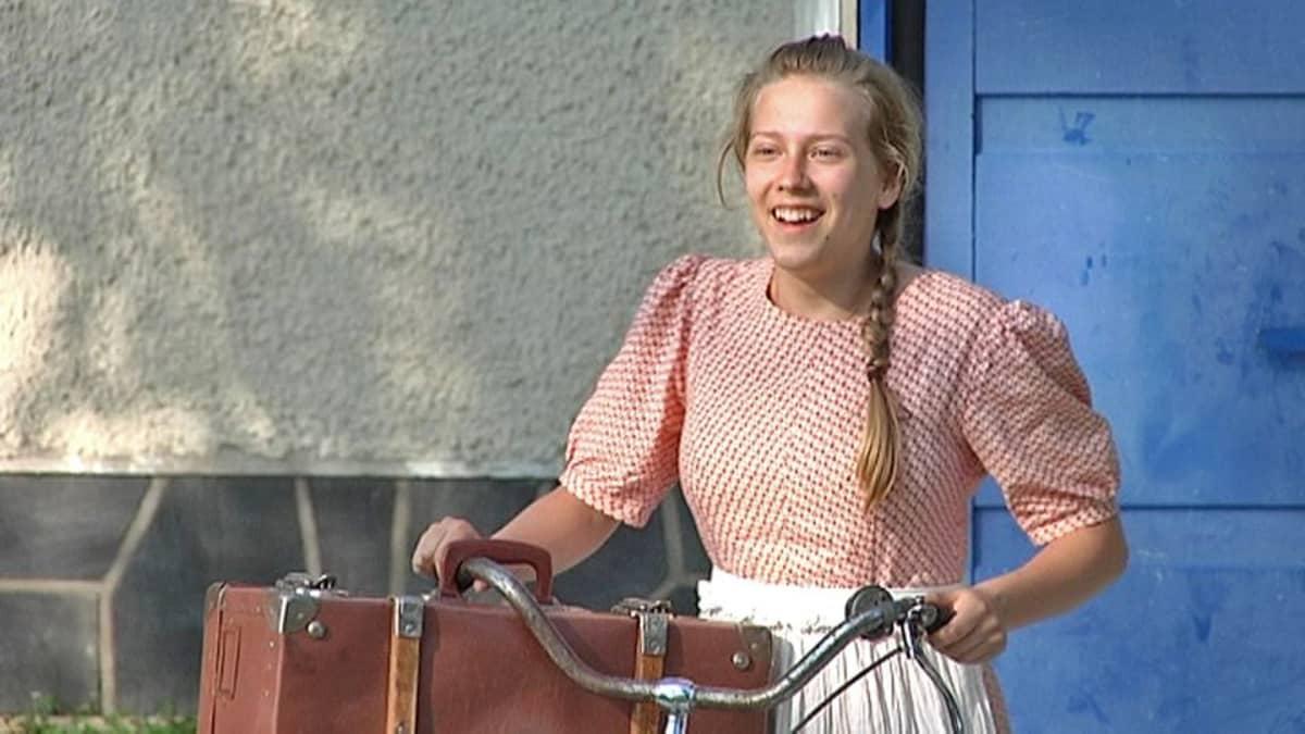 Nuori tyttö taluttaa polkupyörää ja hymyilee.