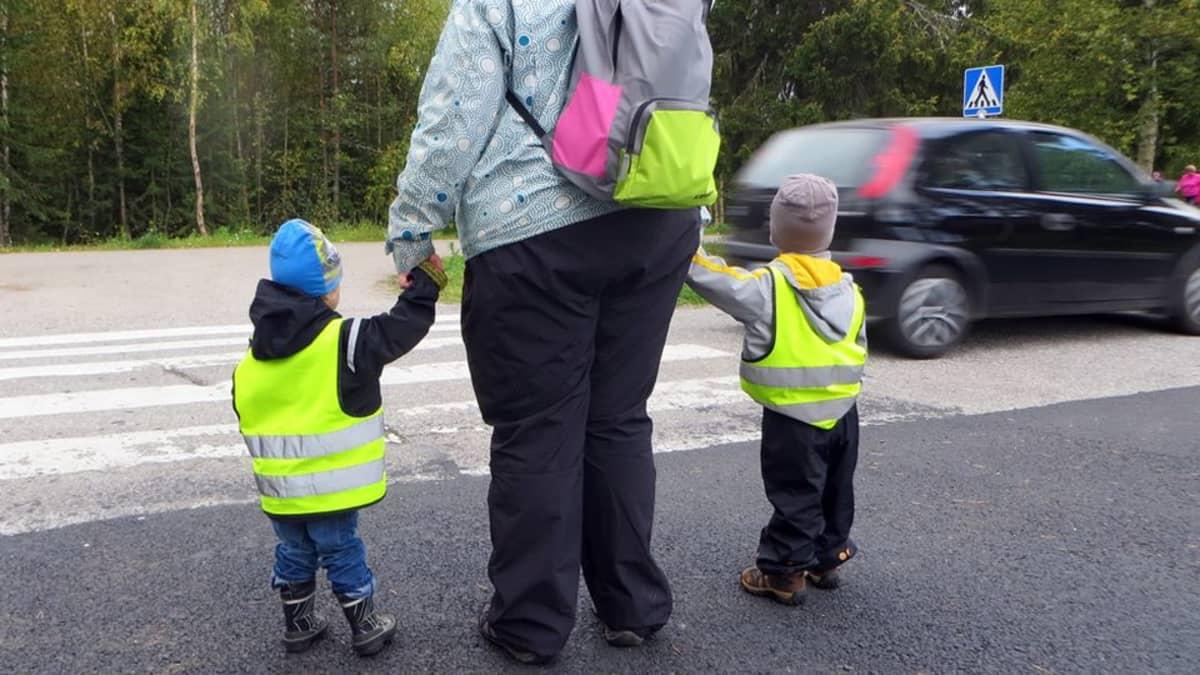 Lapset ylittämässä suojatietä hoitajan kanssa.