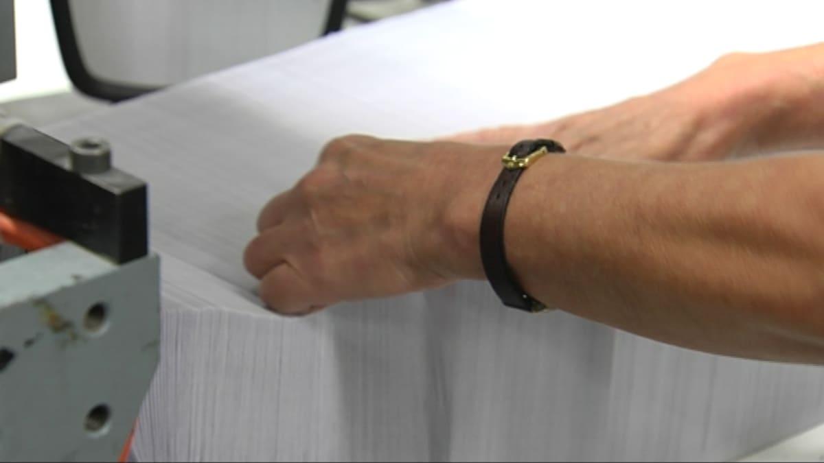 Kirjekuoritehtaan koneessa iso nippu kirjekuoria ja työntekijän kädet tekemässä töitä