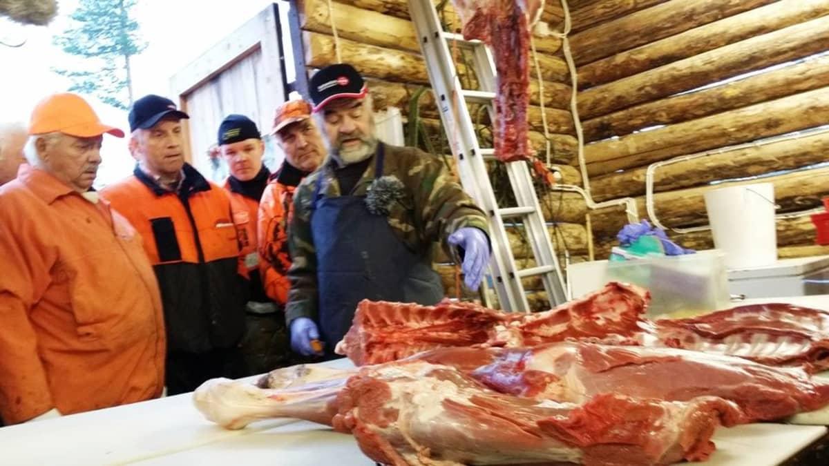 Lihamestari Erkki Halonen näyttää lihanleikkaamisen mallia Isokylän miehille