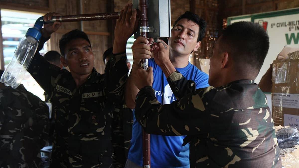 Liter of Light –järjestön perustaja opettaa sotilaille, miten muovipullosta tehdään katulamppu.