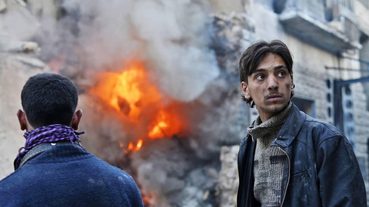 Kaksi miestä ja heidän takanaan palava rakennus.