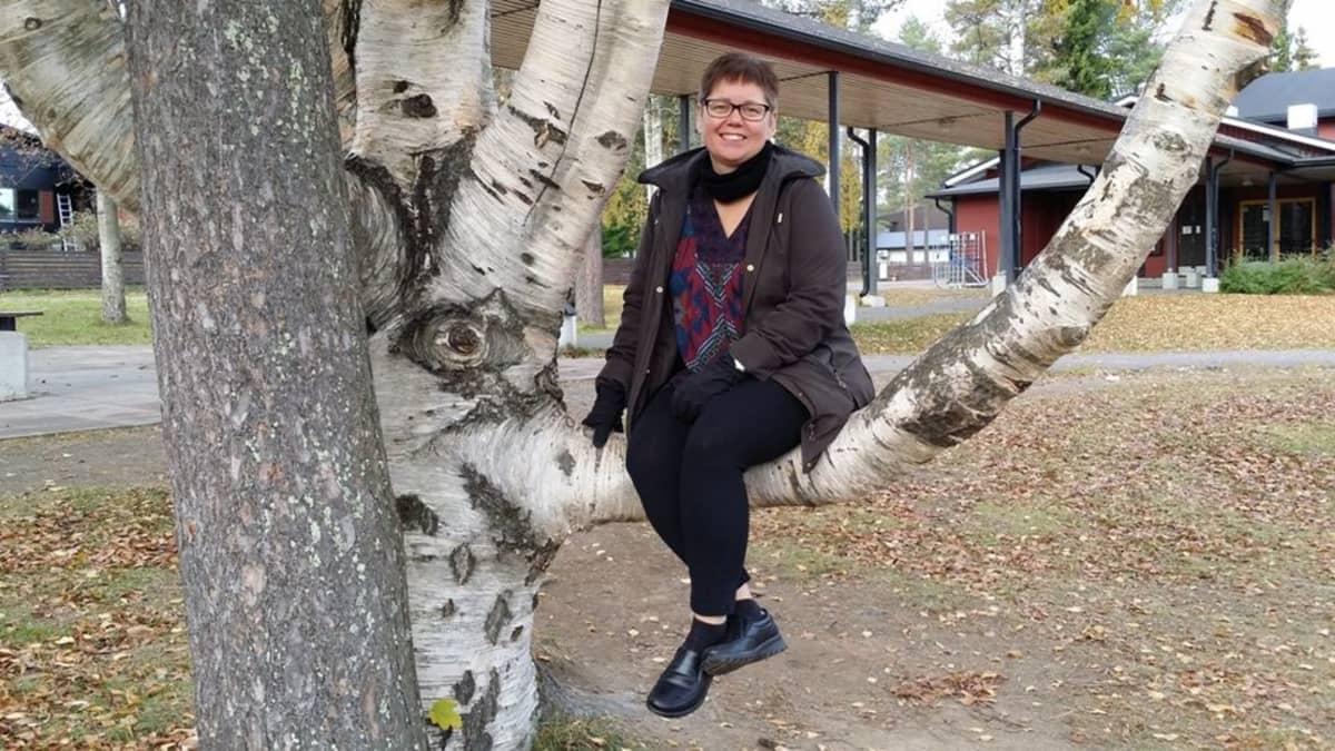 Pia Järvi istuu paksun koivunoksan päällä Hakalahden koulun pihalla.