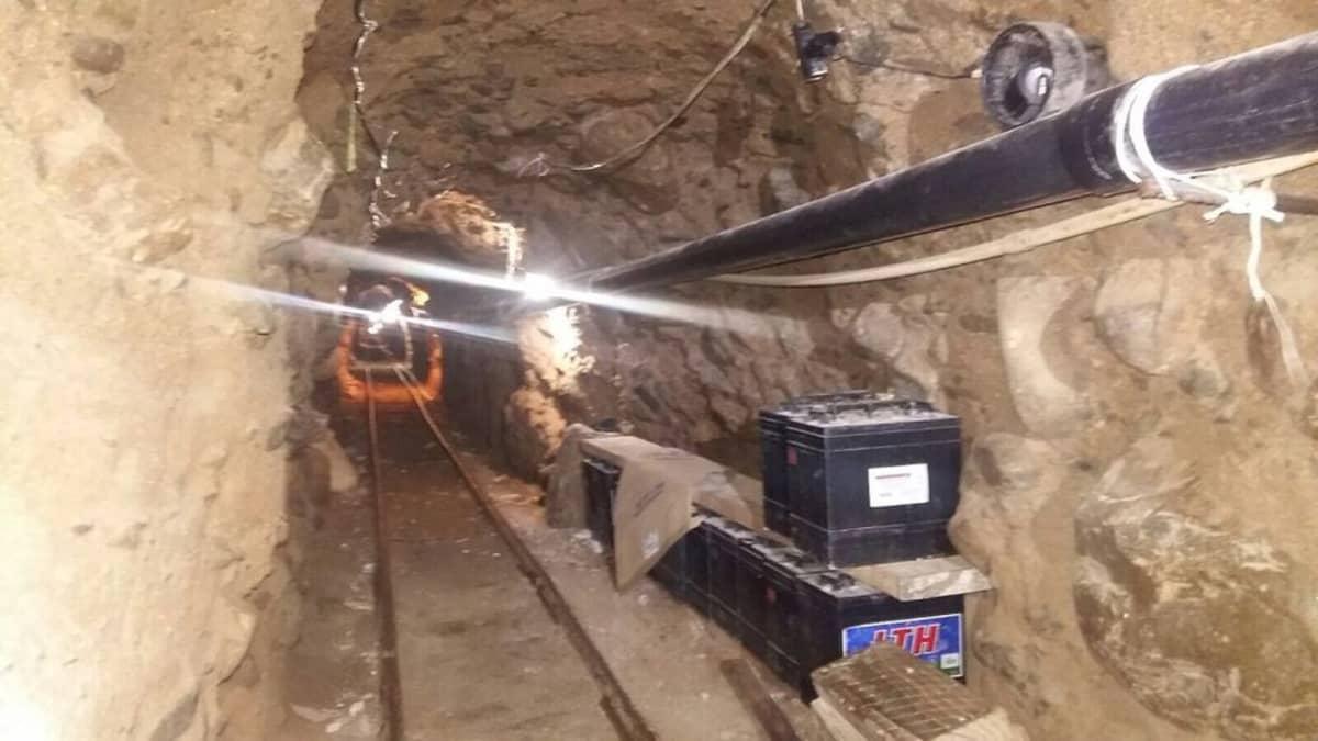 Kuva huumeiden salakuljetukseen käytetystä tunnelista, jossa on kiskot ja valaistus.