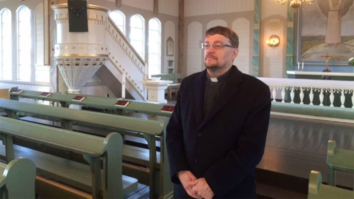 Kirkkoherra Raimo Kytölä Perhon kirkossa, taustalla saarnastuoli ja osa alttaritaulua.