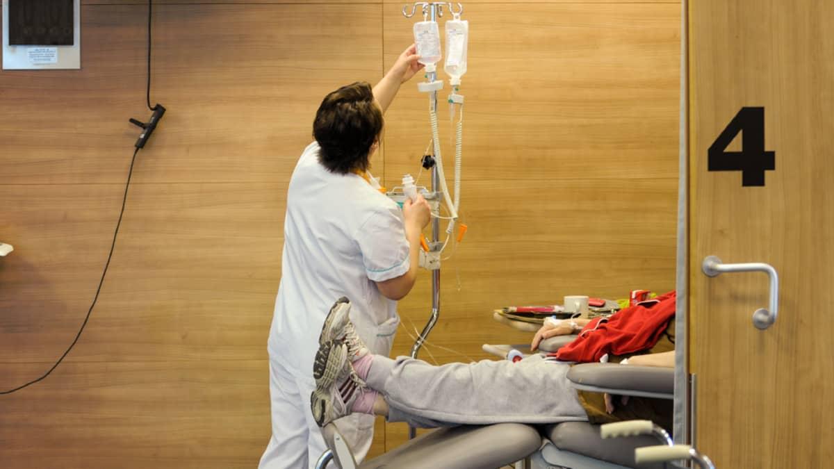Sairaanhoitaja tarkastelee potilaan tiputuspulloa.