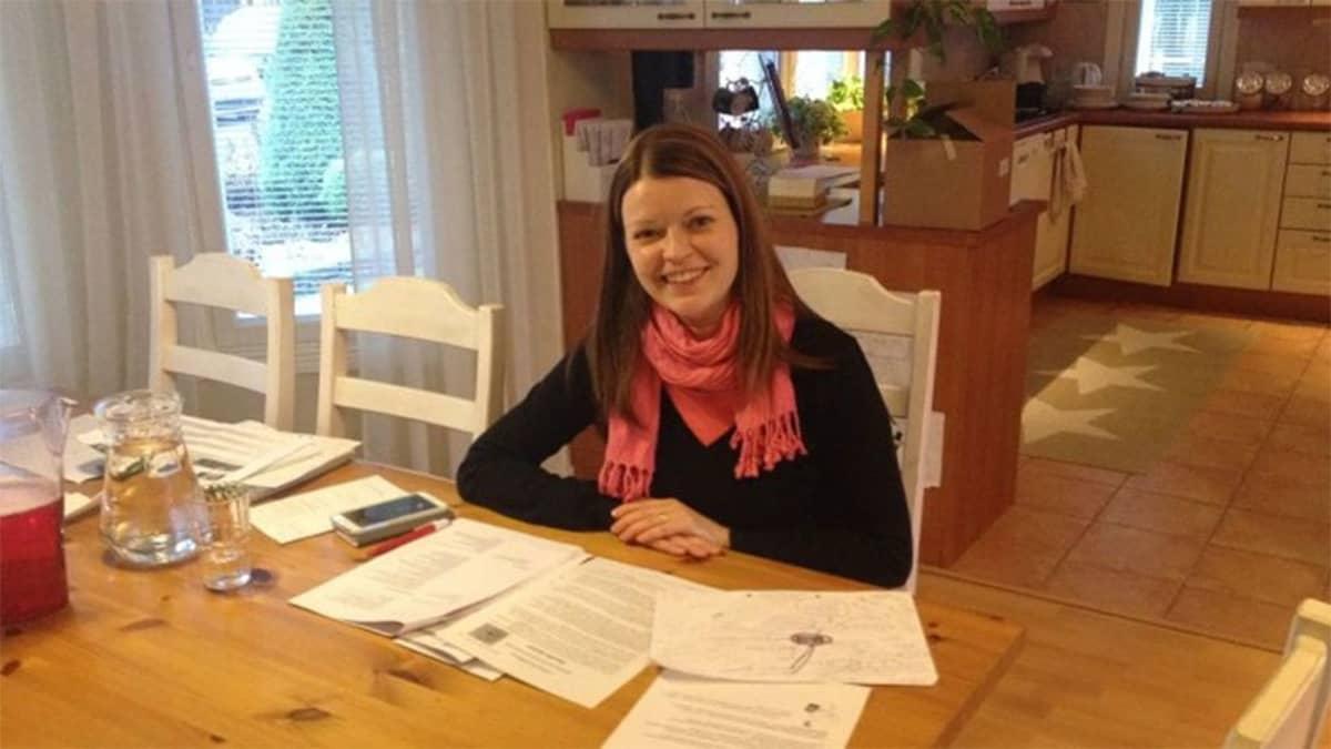 Annika Sandkvist istuu keittiössään, pöydällä papereita.
