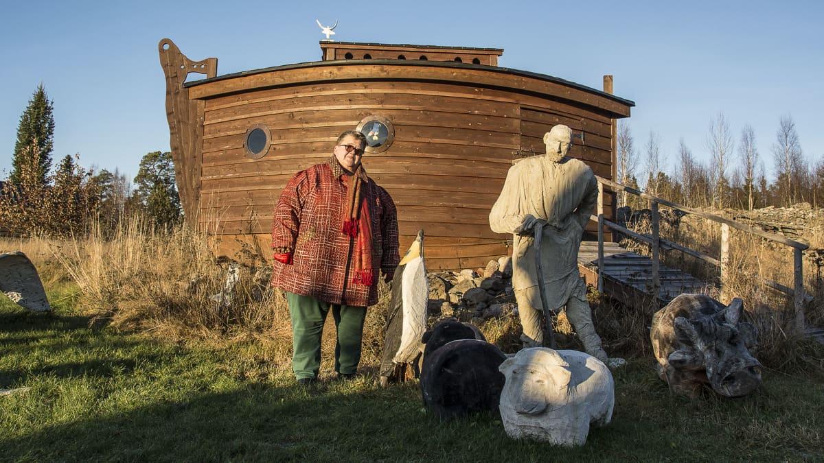 Kuvassa puinen Nooan arkki, Nooa-patsas ja Leena Harjunpää