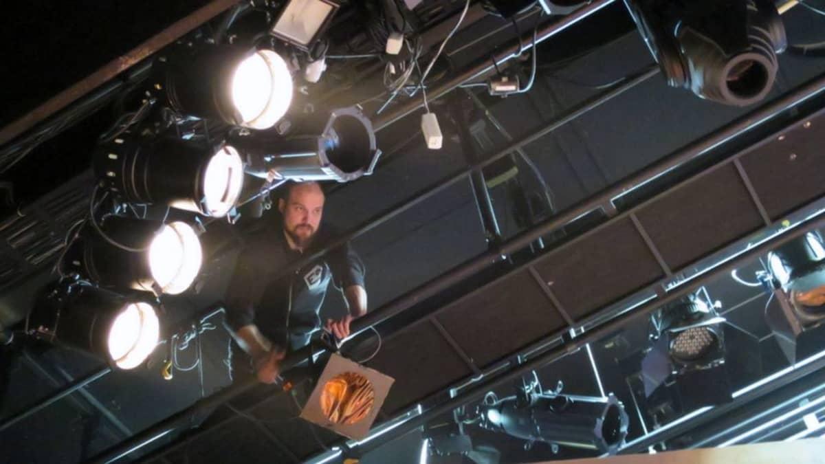 Mies säätää valoja ylhäällä katonrajassa teatterin näyttämöllä