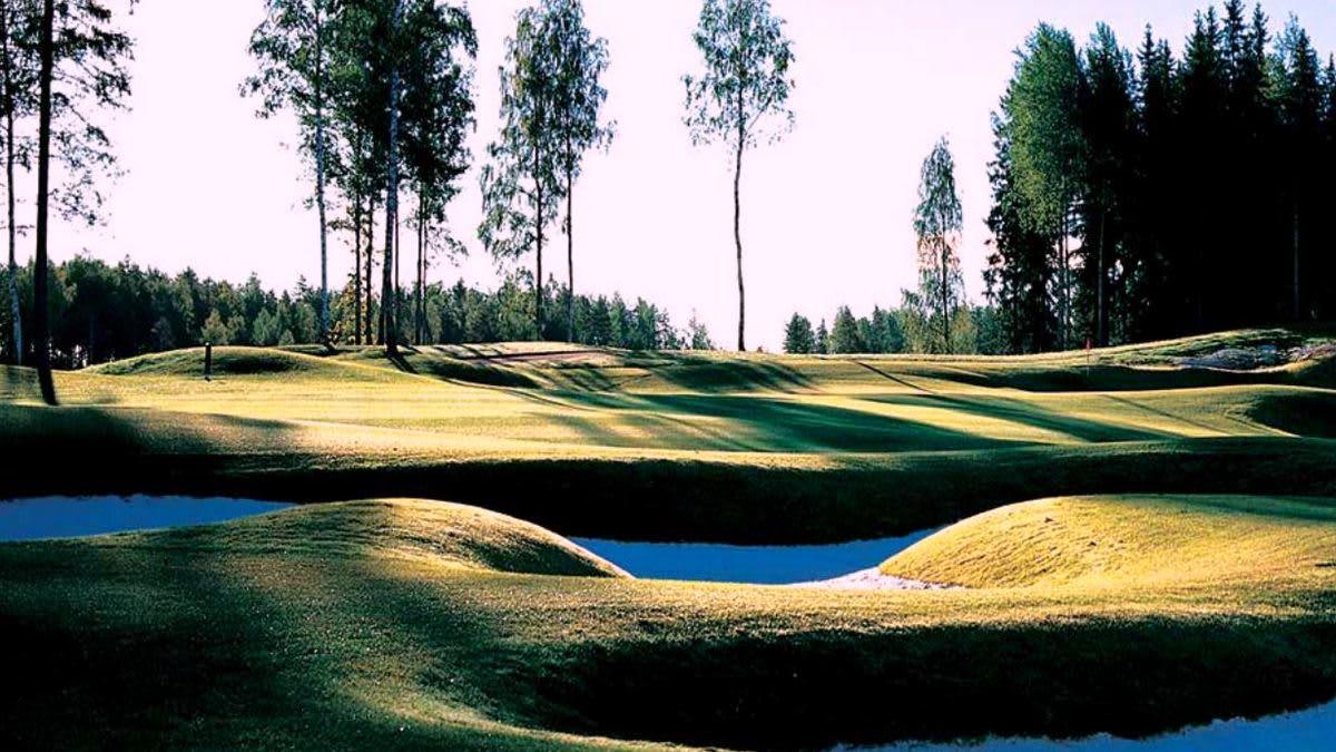 Aurinko laskee greenin taaksen golfkentällä