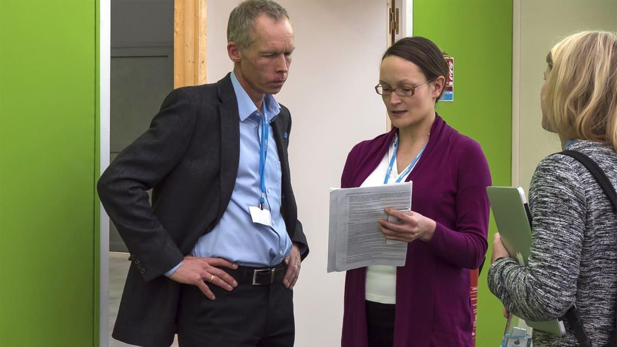 Nainen ja mies katselevat paperinivaskaa.