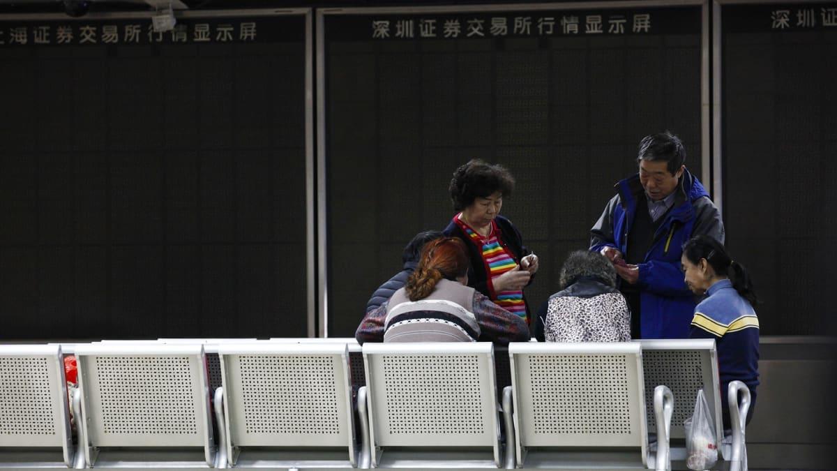 Sijoittajat pelaavat korttia pörssisalin tyhjien näyttötaulujen edessä