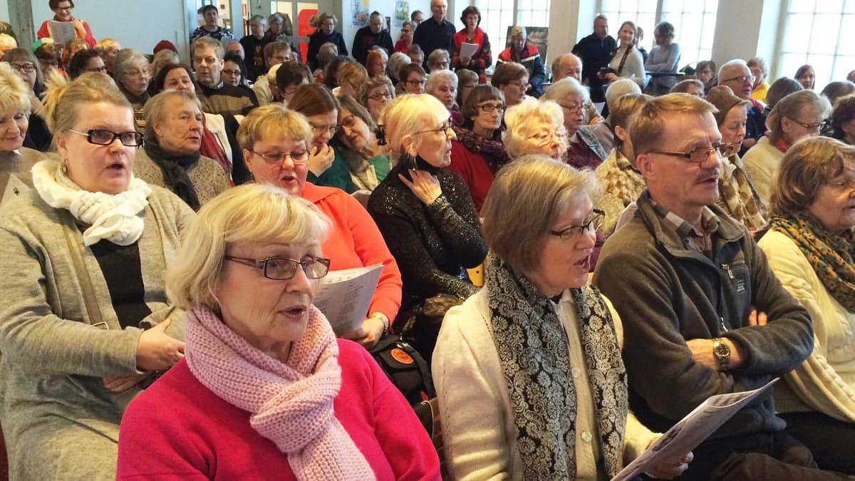 Sali täynnä yleisöä laulamassa vanhoja koululauluja Työväenmuseo Werstaalla Tampereella.