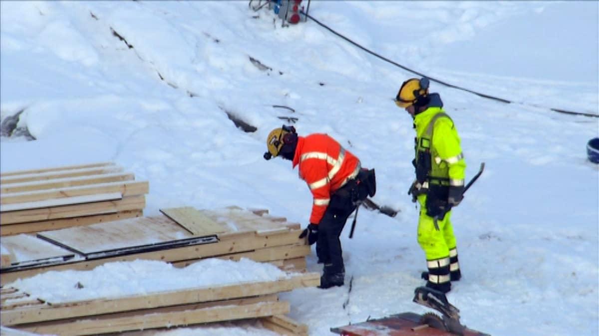 Rakennusmiehet lautakasan äärellä lumihangessa.