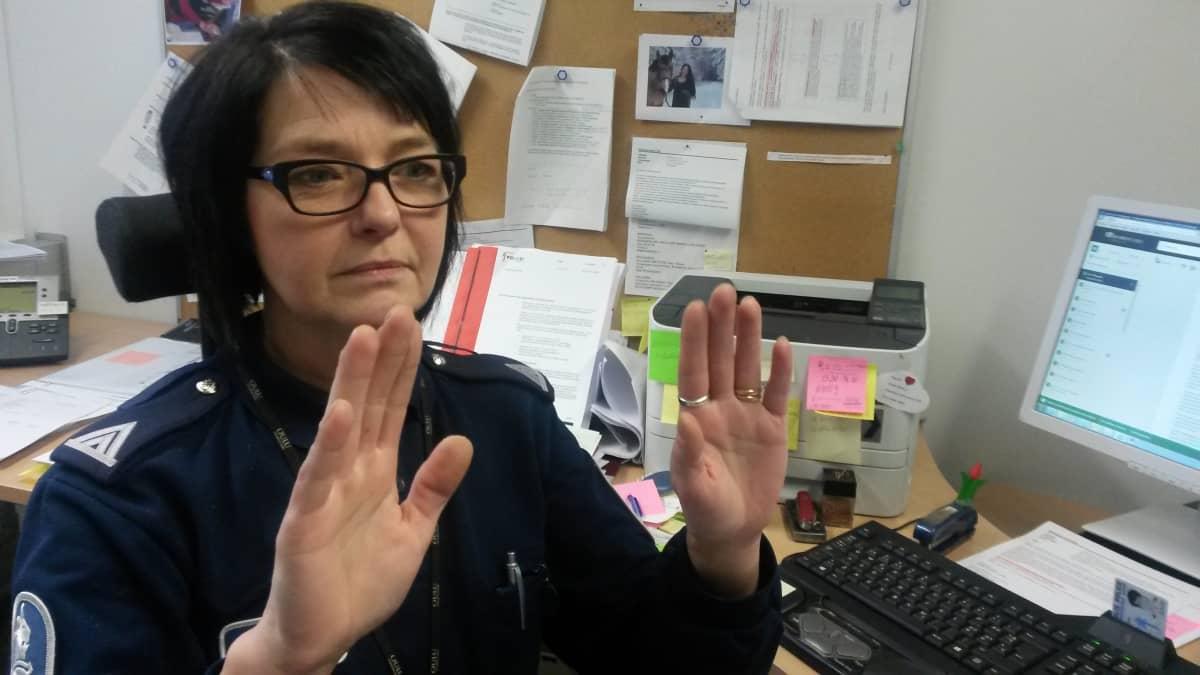Rikosylikonstaapeli Irmeli Korhonen iestuu työhuoneessaan Oulun poliilaitoksella ja näyttää käsillään ei-sanaa.