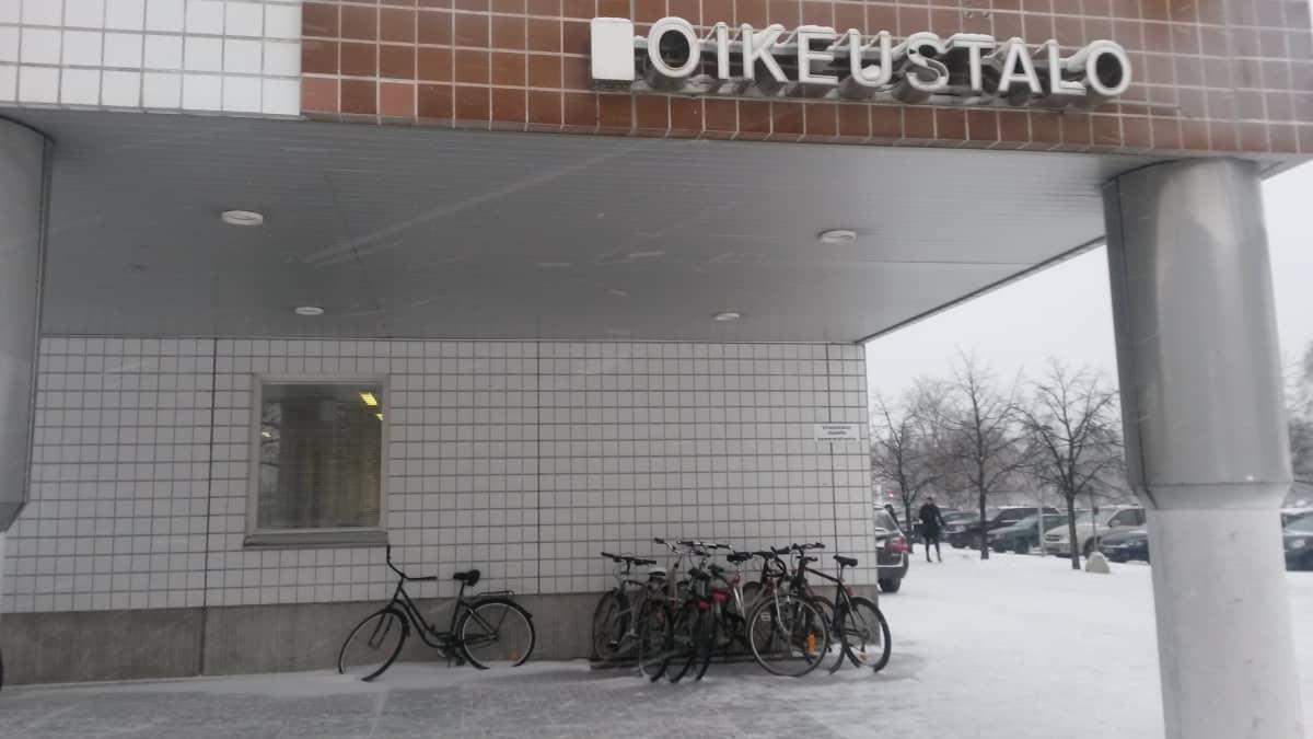 Oulun oikeustalon ulkoseinä talvella ja taustalla lehdettömiä puita.