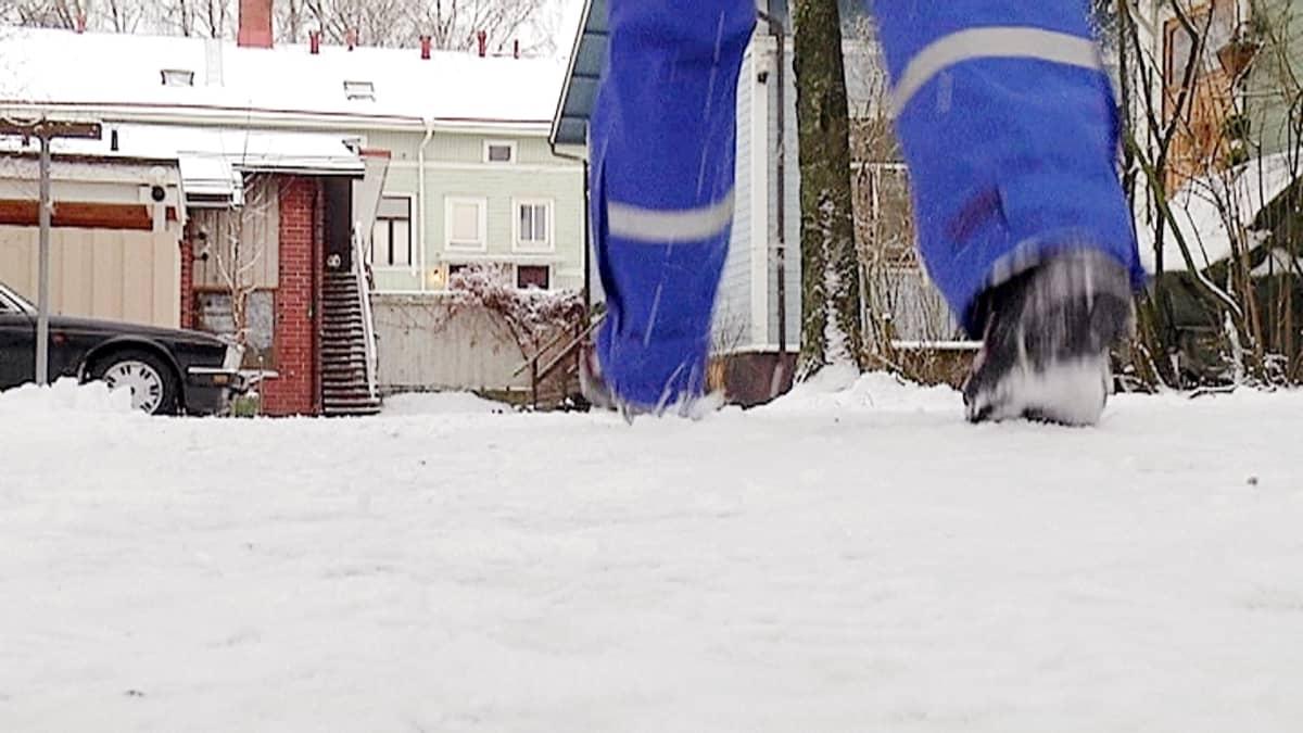 Postinkantaja jakaa postia talvella.