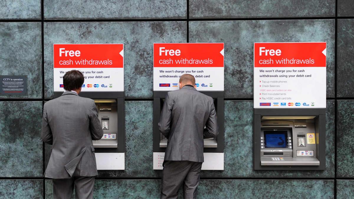 Kaksi pukumiestä raha-automaateilla.