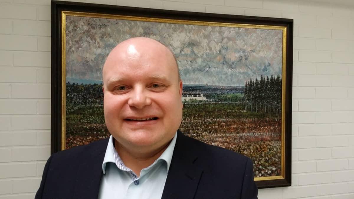 Toimitusjohtaja Juha Jokinen seisoo taulun edessä