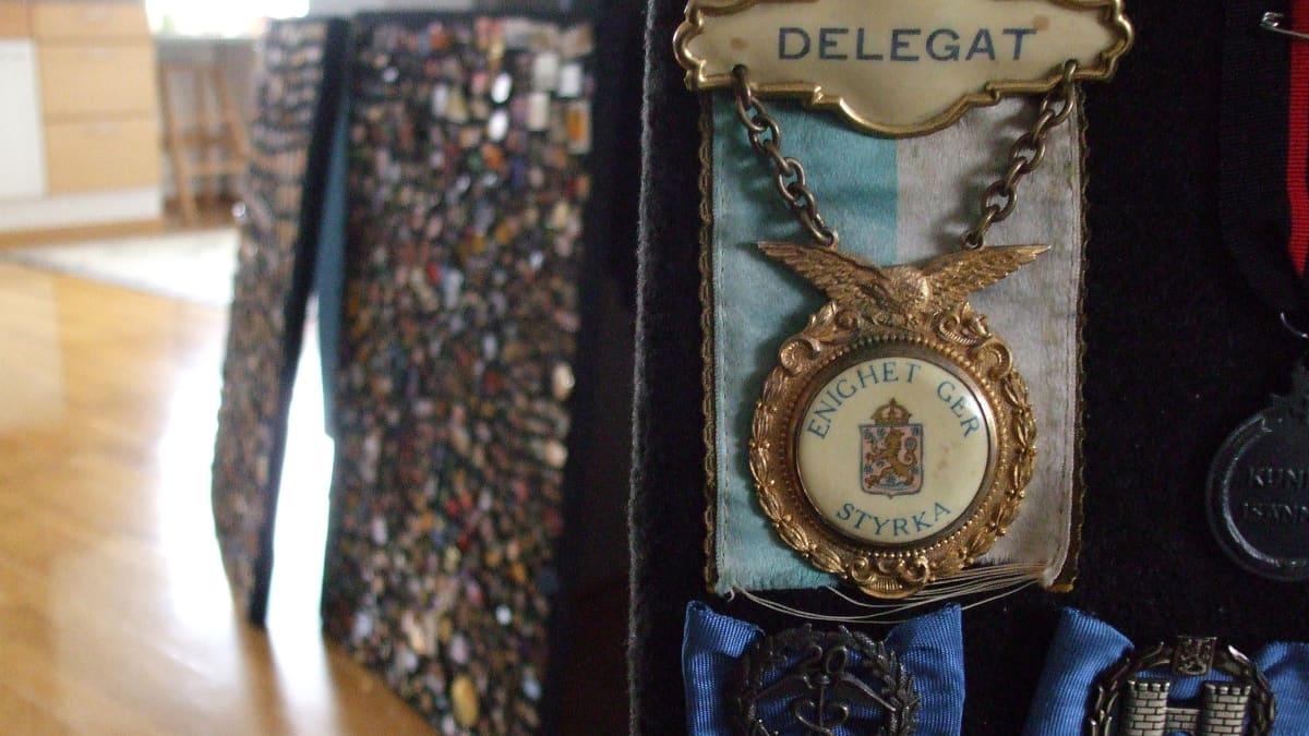 Suuri kaksiosainen rintamerkki, joka roikuu sinivalkoisen nauhan päällä. Yläosassa olevassa pikkulaatassa lukee delegat ja siitä roikkuu ketjuista isompi laatta, jossa  on Suomen leijonavaakuna, jonka päällä lukee  Enighet ger styrka.