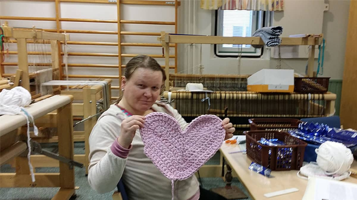 Nina Pyykkönen esittelee virkattua vaaleanpunaista sydäntä työpajassa. Taustalla kangaspuita.