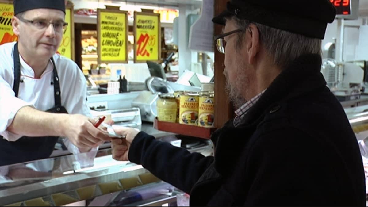 Mies palvelee asiakasta Turun kauppahallissa.