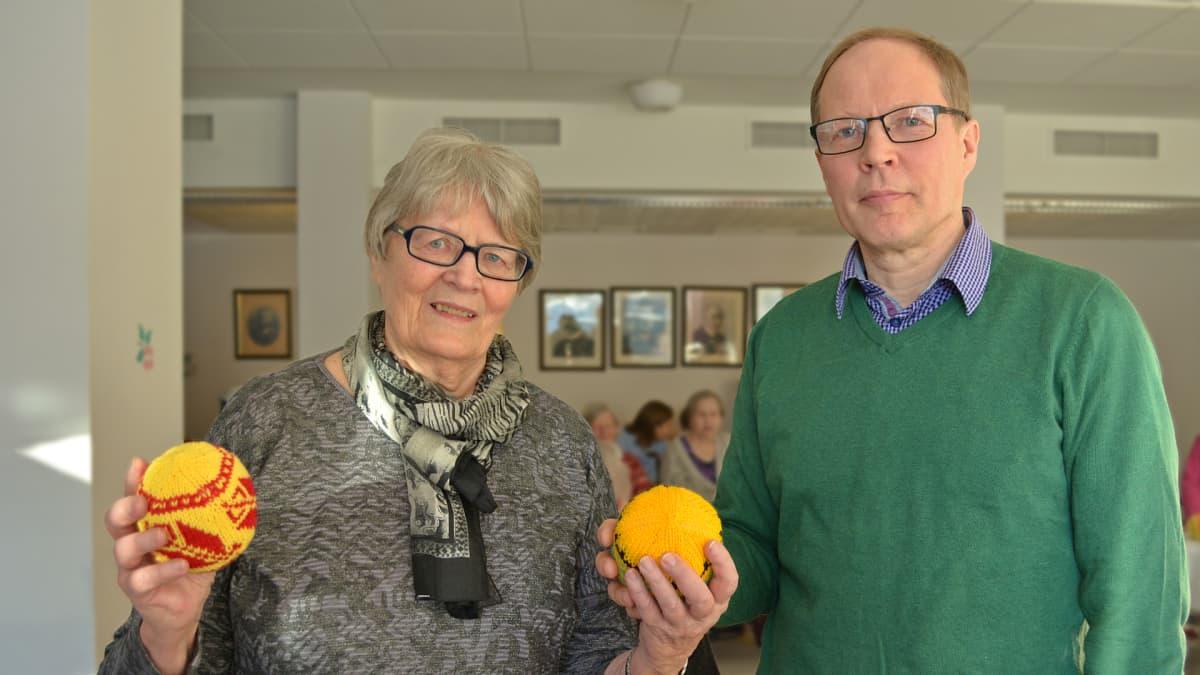 Leena Valtanen ja Arto Kettunen pitelevät neulepalloa käsissään ja katsovat kameraan.