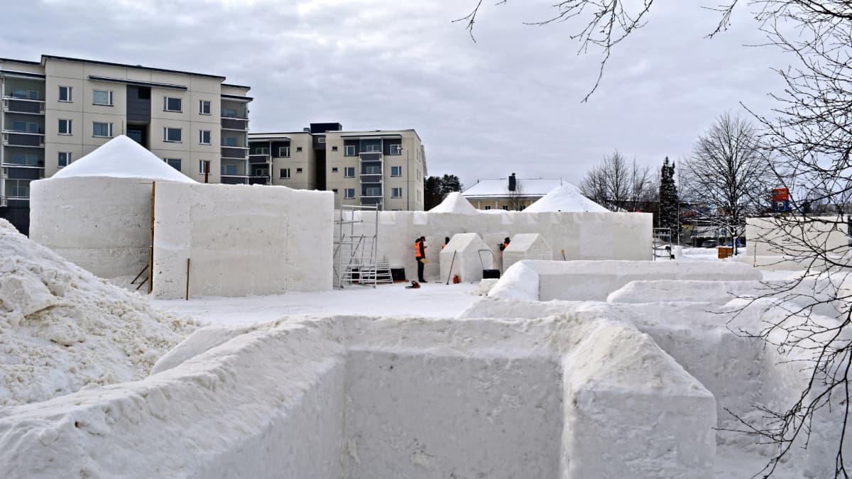 Lumimiilun keskeneräiset lumiseinämät ja lumilinnan rakentajia työssään.